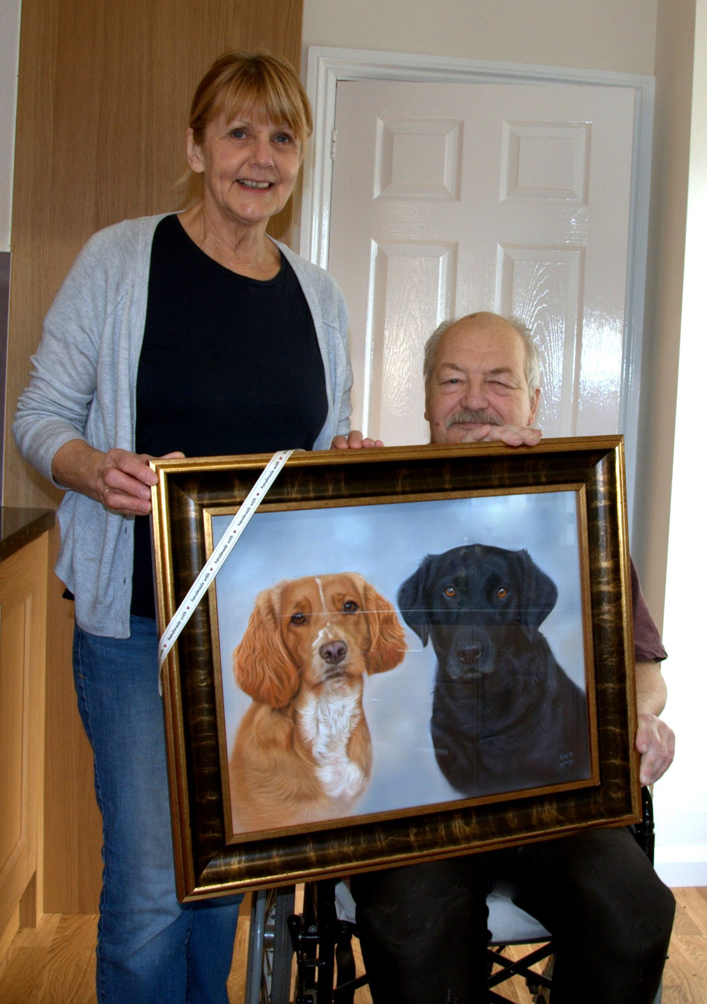 clients holding their painting of two dogs